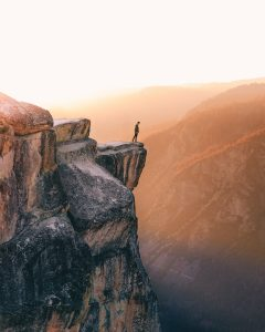 Man standing at edge of massive cliff