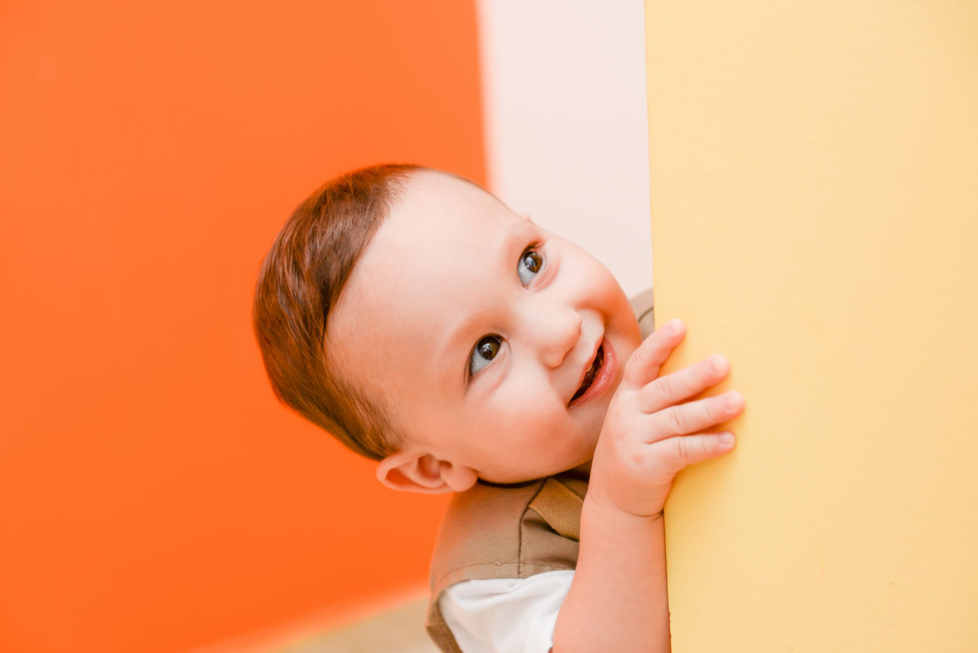Smiling toddler peeking around corner