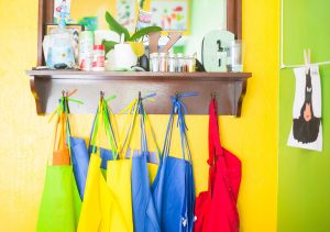 Colourful aprons hanging on hooks