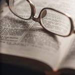 Glasses sitting on open Bible