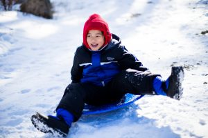 Boy in winter gear sledding